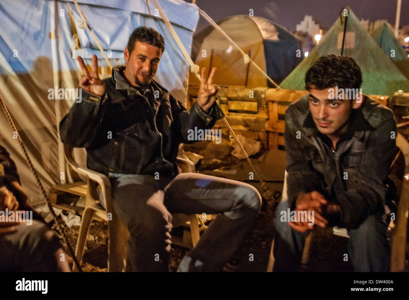 Young protesters gather by a fire in the tent city established in Martyr's Square, Beirut, Lebanon, during the Cedar Stock Photo