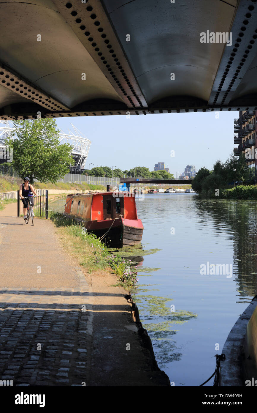 Cycling along the River Lee Navigation at trendy Hackney Wick, East London, UK, the Queen Elizabeth Olympic Stadium behind - Stock Image