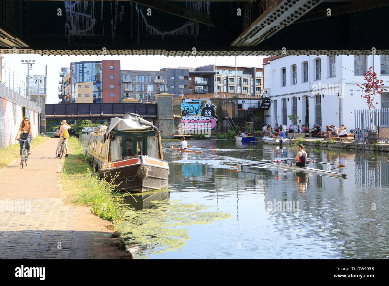 Cycling and rowing along the River Lee Navigation at trendy Hackney Wick, East London, UK - Stock Image
