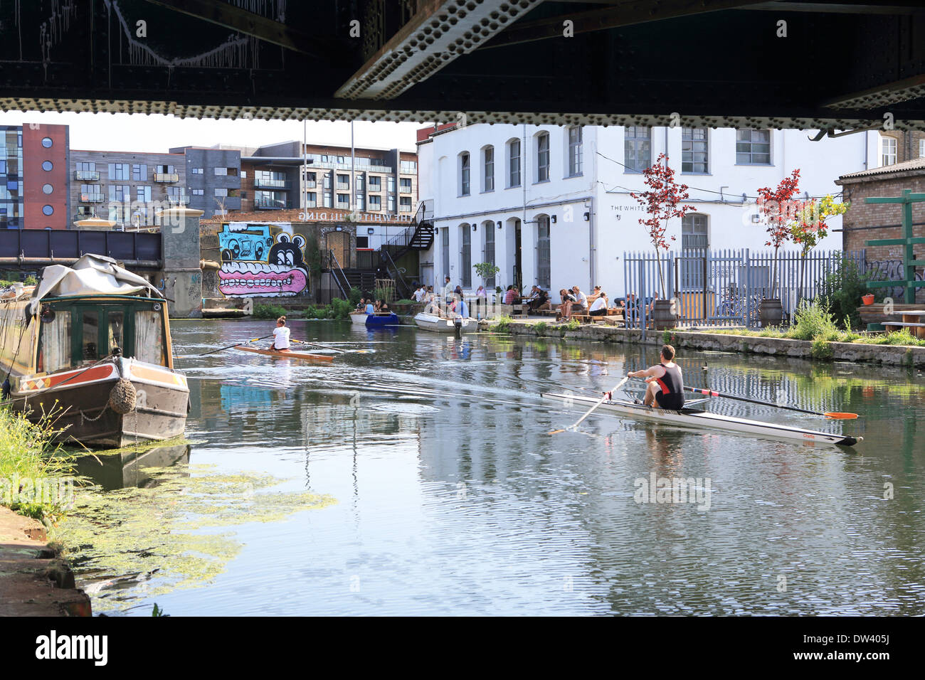 Rowing past the White Building, on the River Lee Navigation, next to White Post Lane, in Hackney Wick, in East London - Stock Image