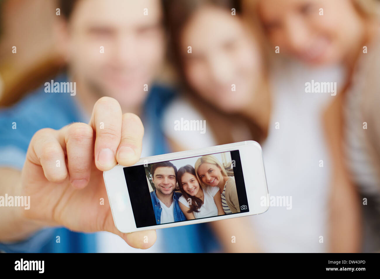 Male hand holding cellular phone with image of happy family of three looking at camera - Stock Image