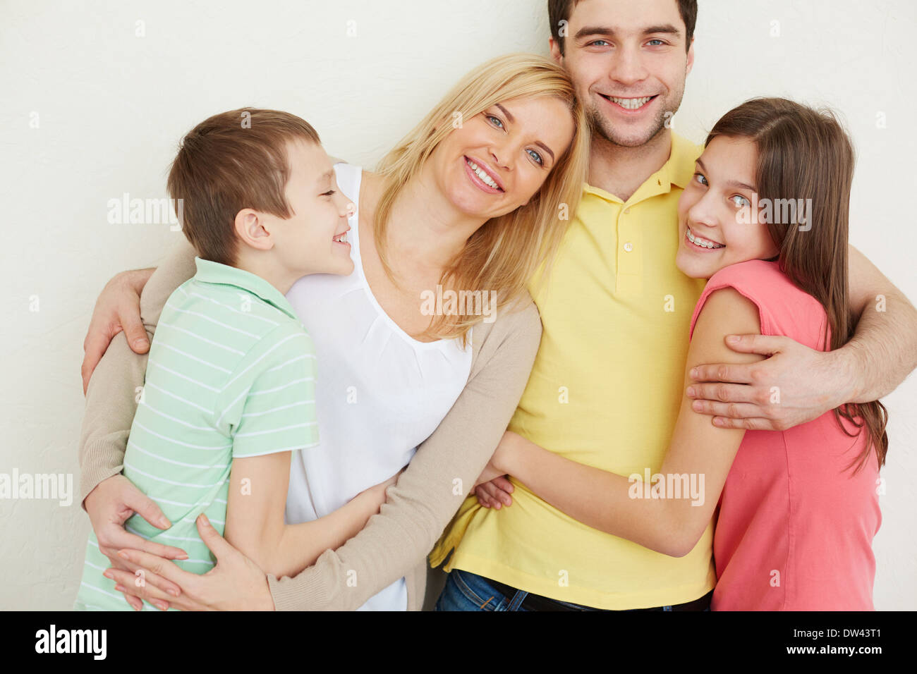 Portrait of affectionate family of four embracing Stock Photo