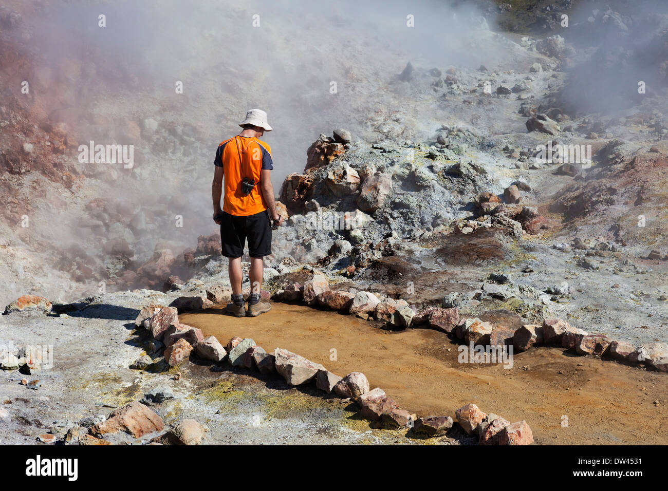 Walker on the Laugavegur Hiking Trail Examining an Active Geothermal Area on the Slopes of the Brennisteinsalda Volcano Iceland - Stock Image