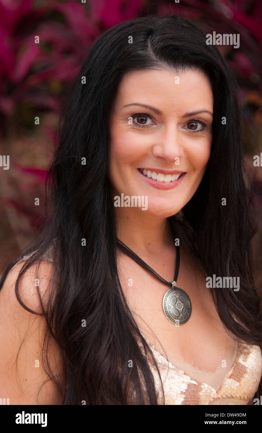 attractive woman in her 40's portrait and smile and energy outdoors - Stock Image