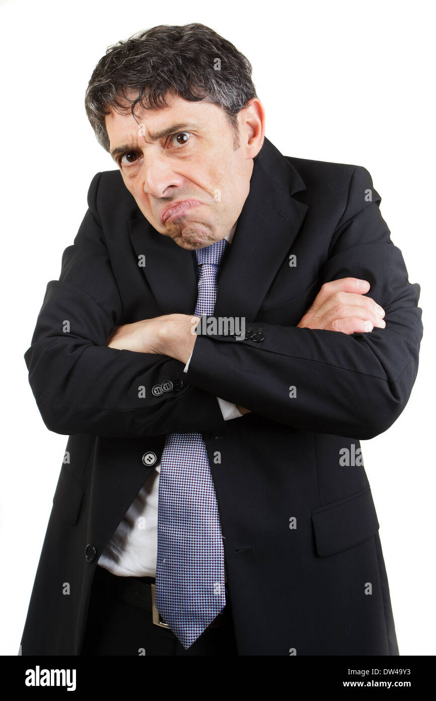 unhappy businessman standing with his arms folded grimacing and glowering at the camera with a sullen expression, isolated. - Stock Image