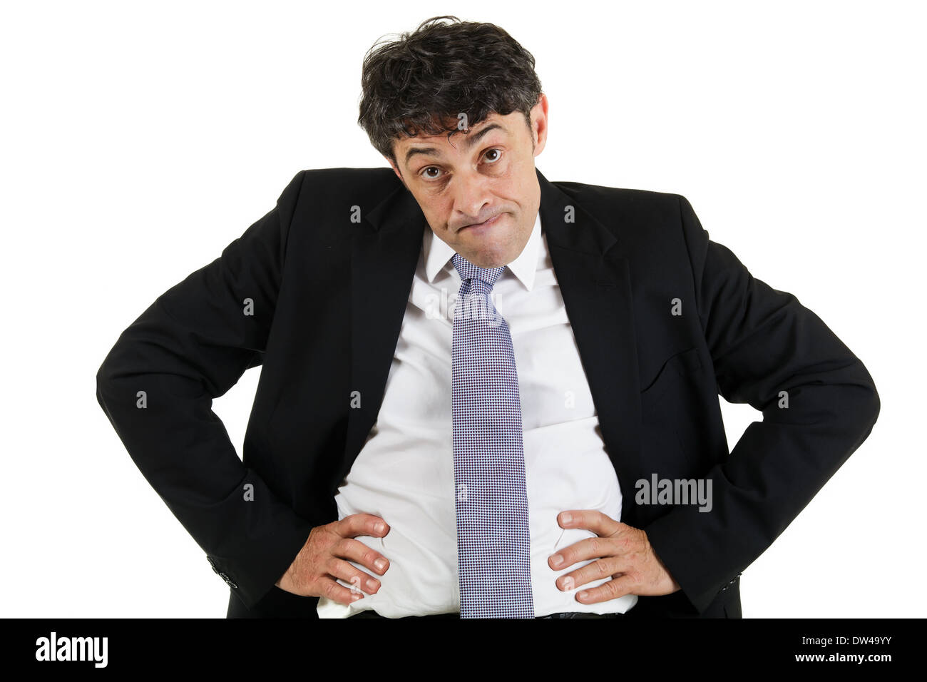 Businessman emphasising a point standing with his hands akimbo on his hips and head lowered glaring with raised eyebrows - Stock Image