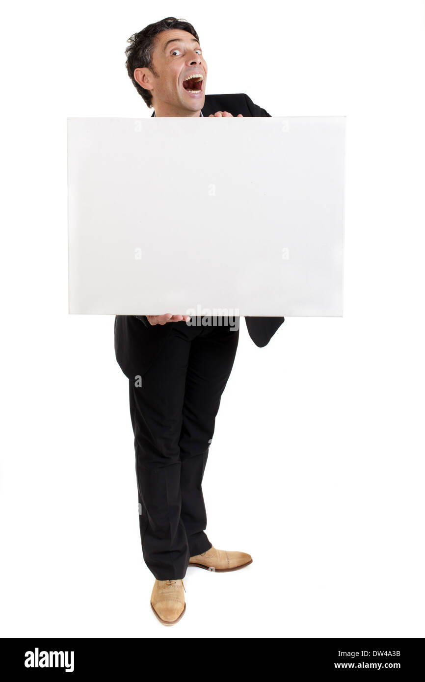 businessman holding a blank white card or sign in front of his chest with an exaggerated open-mouthed look of amazement - Stock Image