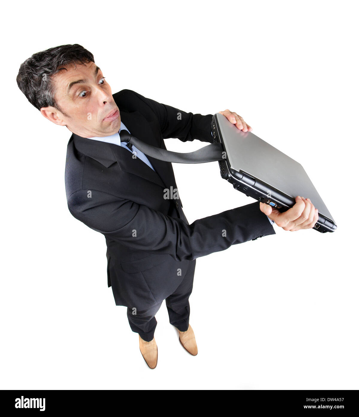 Businessman with his tie caught in his closed laptop computer tugging at it with a look of astonished frustration - Stock Image