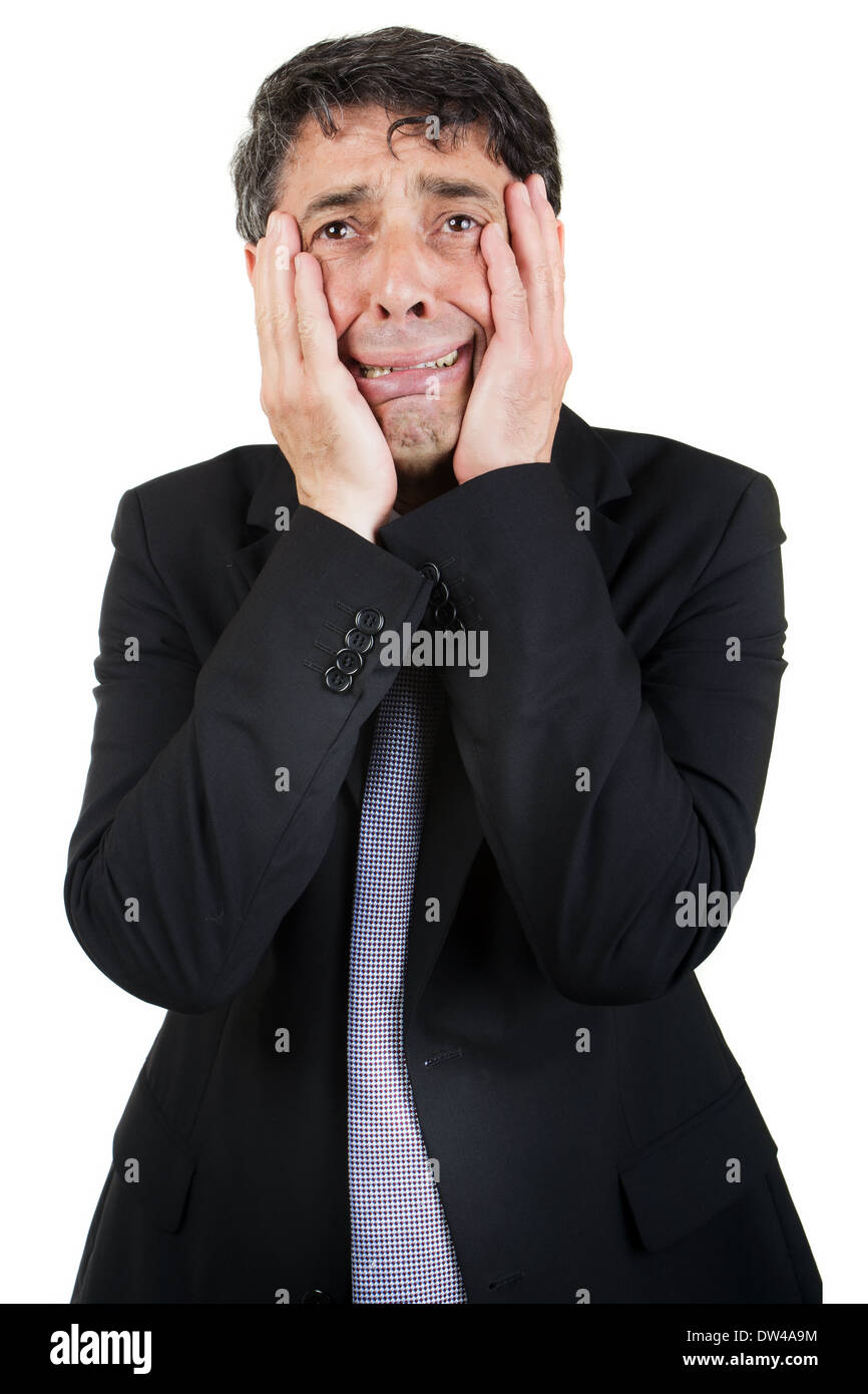 Griefstricken businessman holding his face in his hands as he cries to himself with a woebegone expression, isolated on white - Stock Image