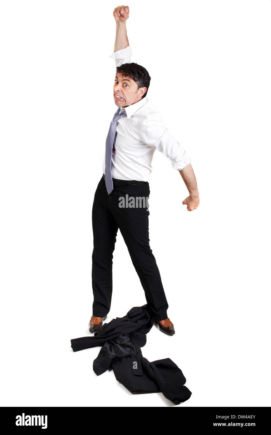 mature businessman throwing his jacket down on the floor in frustration and anger and raising his fist in the air belligerently - Stock Image