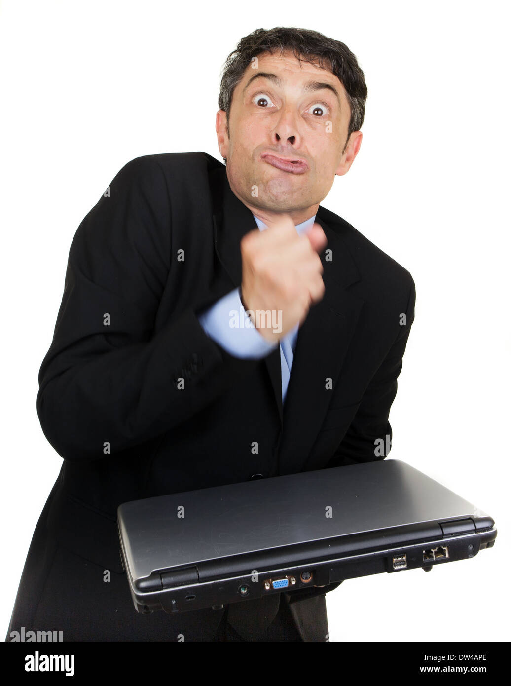 Exasperated man making a fist over his closed laptop computer which he is holding i his hand while grimacing at the camera - Stock Image
