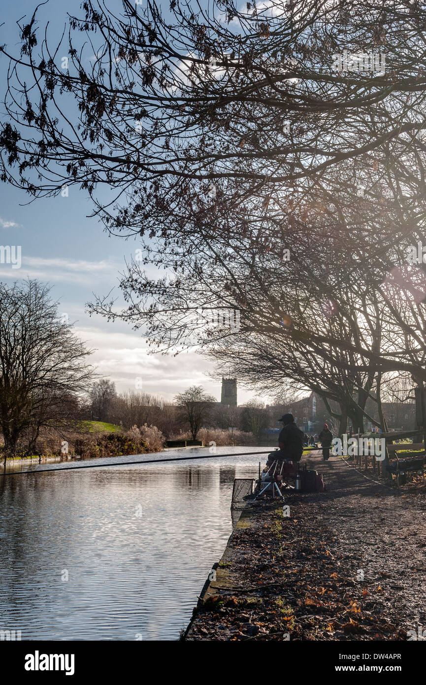 Fishermen and walker on canal in Middlewich, Cheshire, with parish church in background and winter trees in foreground. - Stock Image