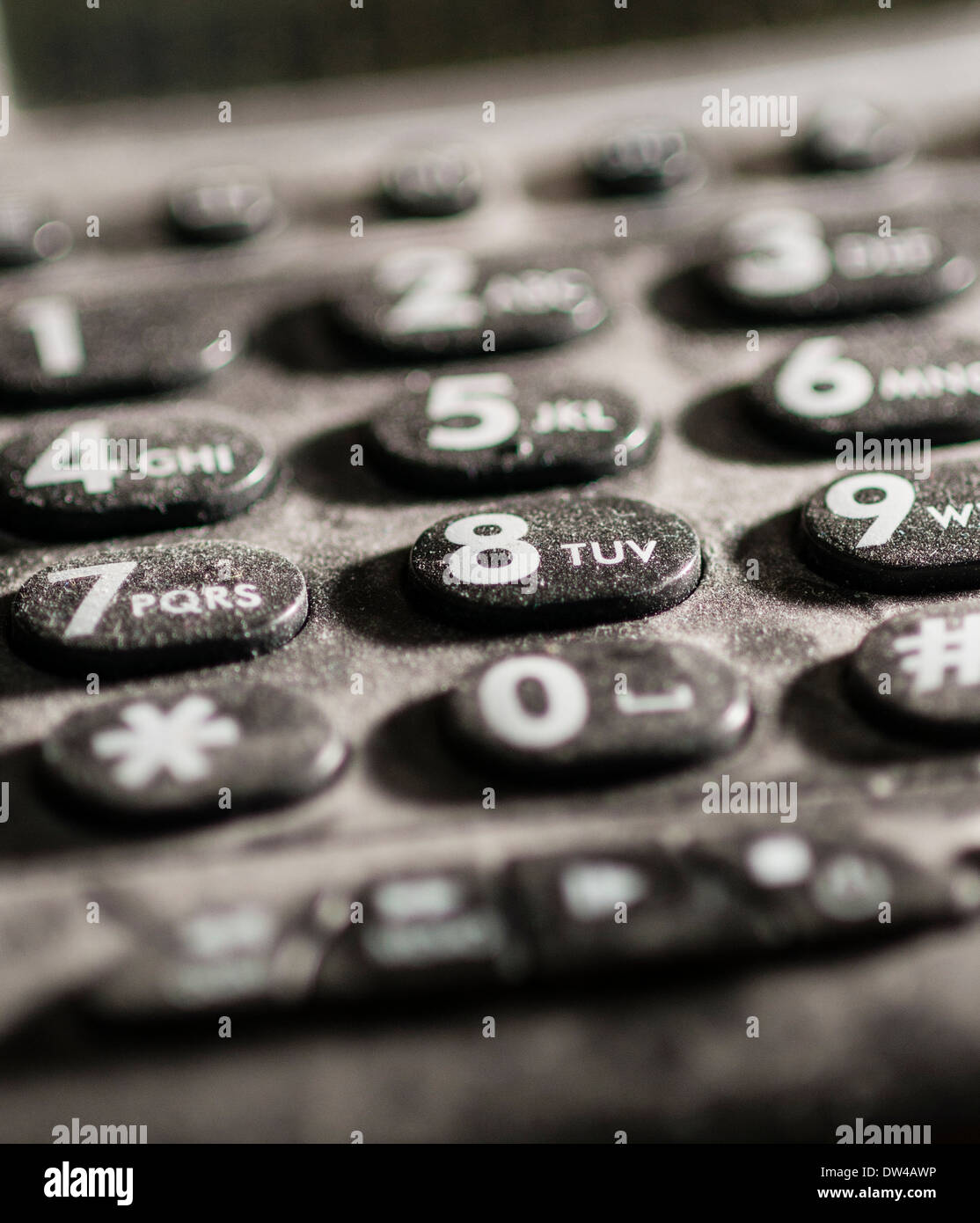 Close up of dusty telephone key pad, side lit, shallow depth-of-field. - Stock Image