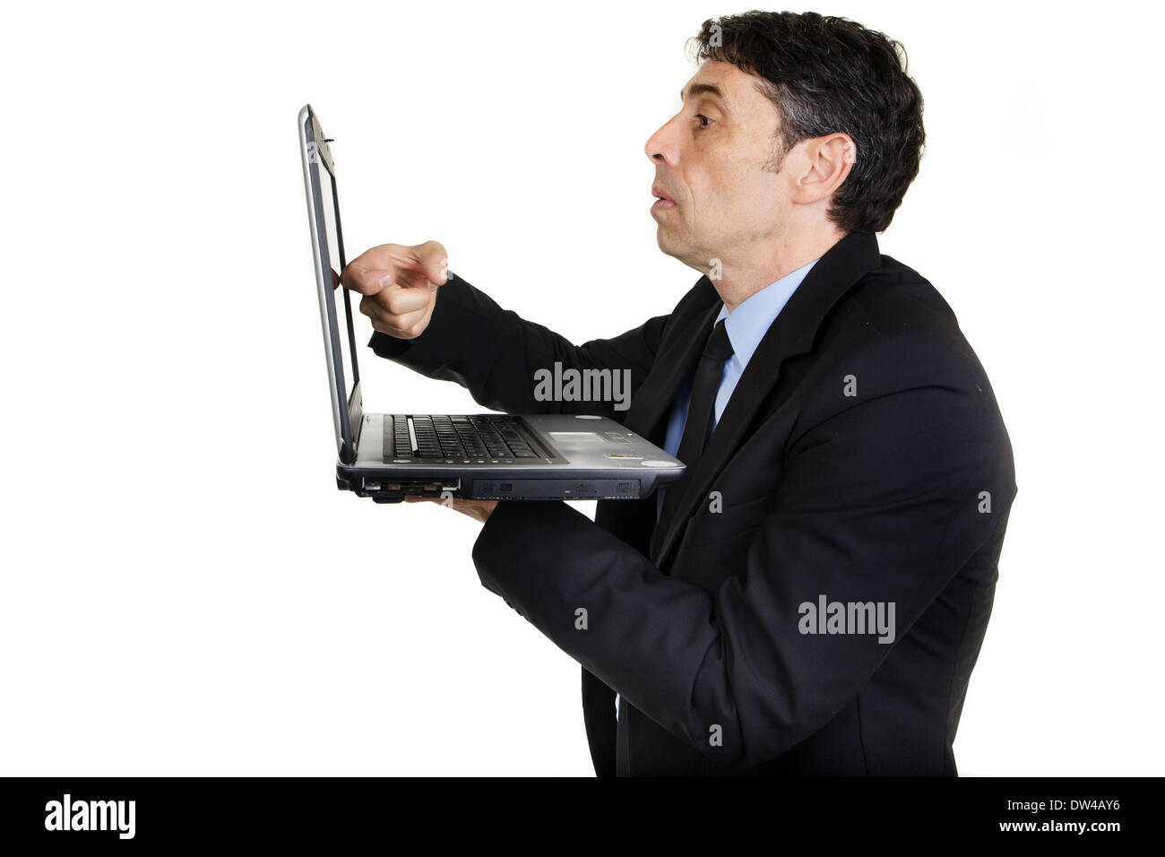 Side view of a serious businessman tapping his laptop screen with his finger as he stands holding it in his hand - Stock Image