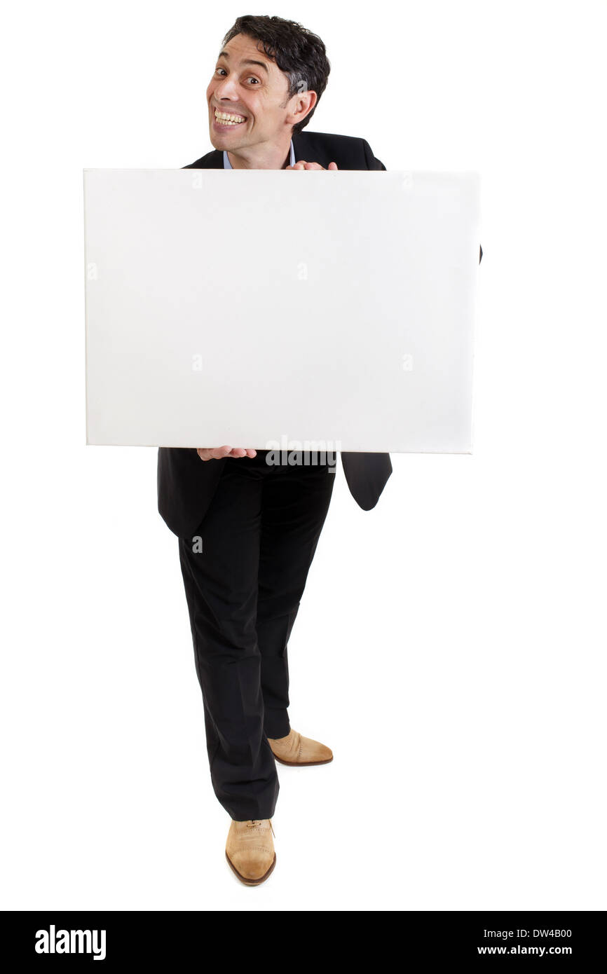 Smart, middle-aged businessman with a cheesy insincere toothy grin holding a blank white sign in his hands with copyspace - Stock Image