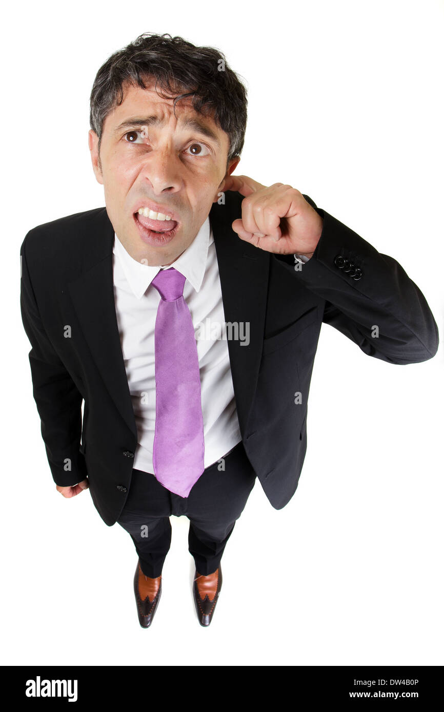 Business man looking up with a puzzled expression scratching his ear in total bewilderment or stupidity, fun high angle portrait - Stock Image