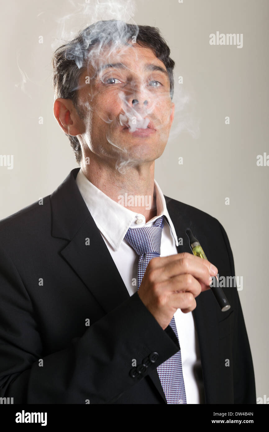 Middle aged confident man enjoying smoking an e-cigarette or vaporizer exhaling a cloud of smoke and peering through - Stock Image