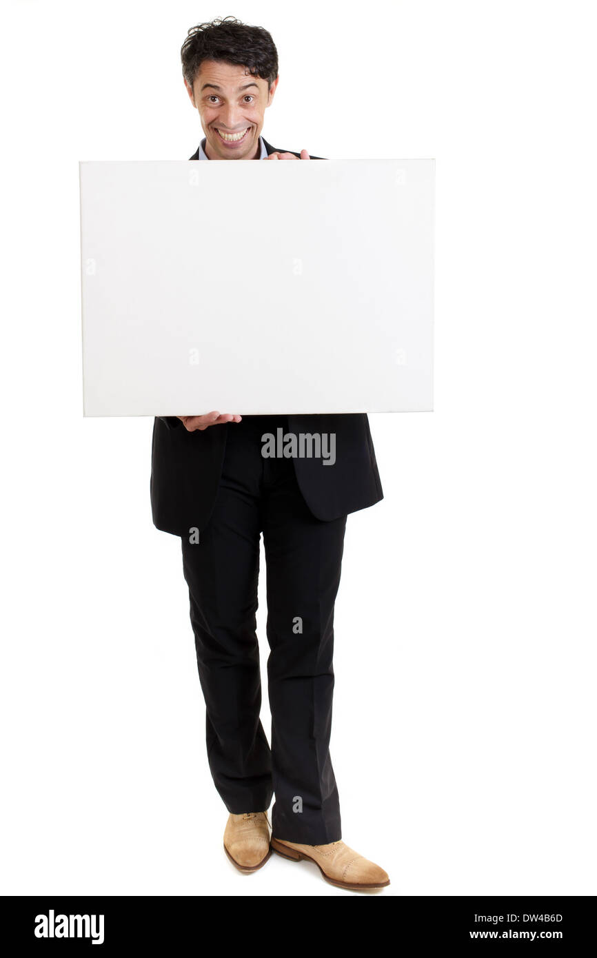 Persuasive middle-aged man with a big smile holding a blank sign in front of his chest . - Stock Image