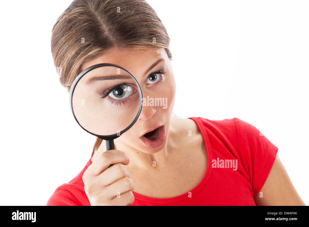 Girl looking through a magnifying glass and looking surprised, isolated on white - Stock Image