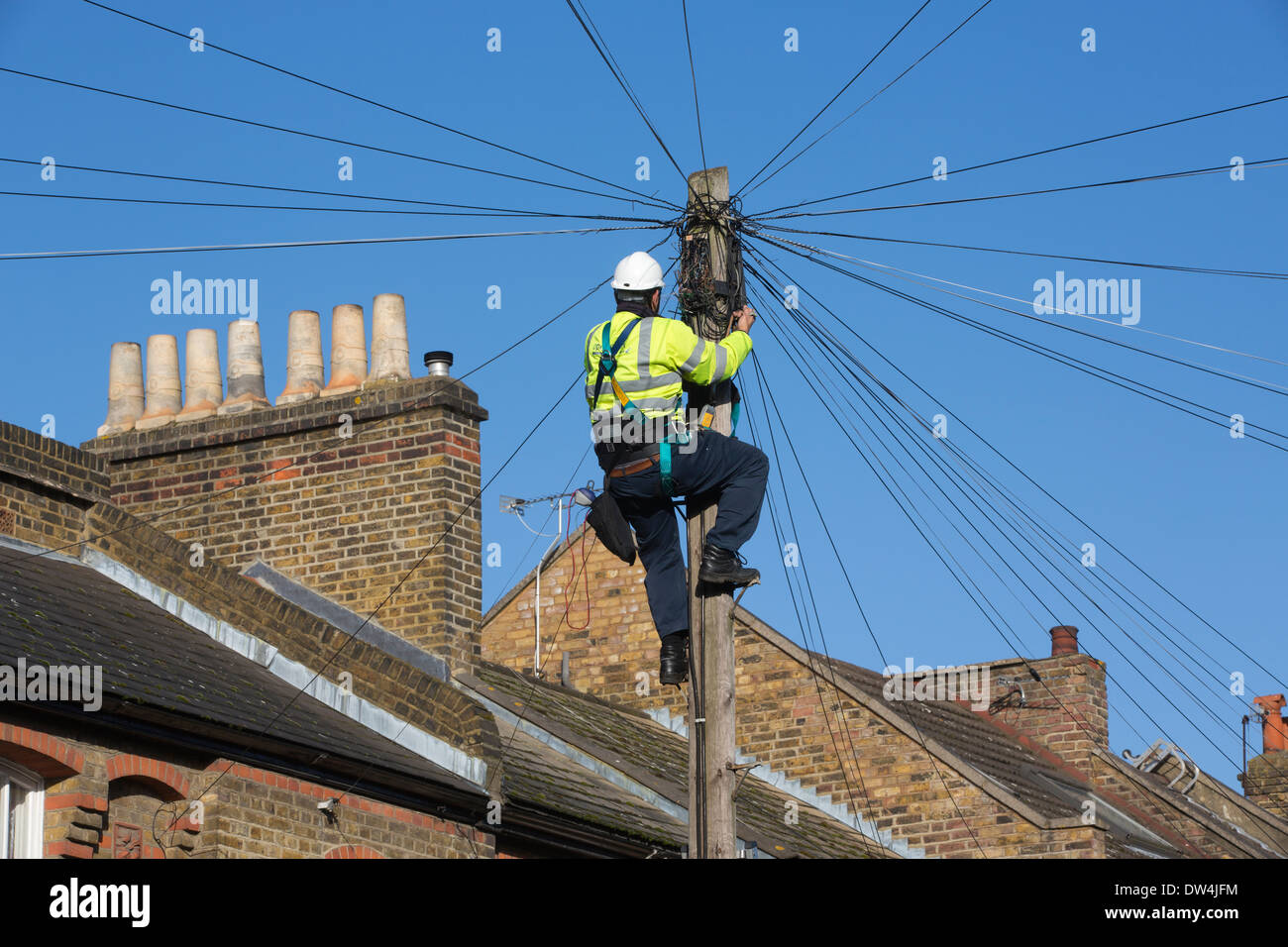 Telecommunications engineer working on an overhead telephone communications pole amongst terraced houses in London, UK - Stock Image
