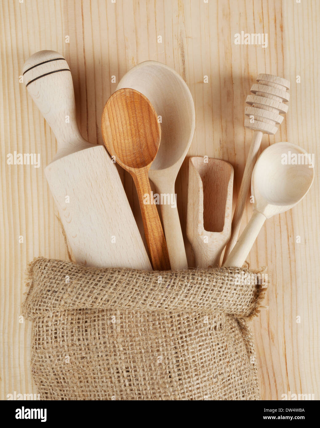 wooden kitchen utensils:spoons, rolling pin, scoop and honey dipper in sack - Stock Image