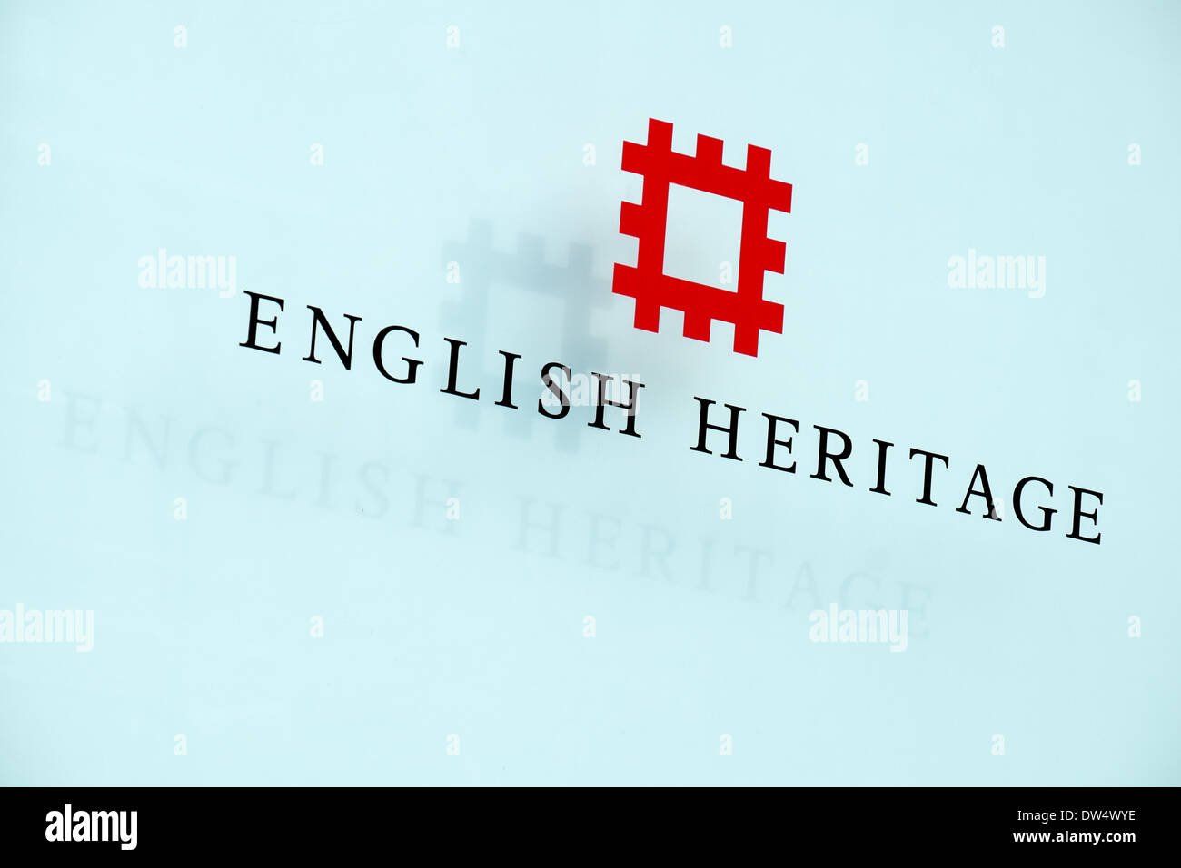 The English Heritage logo & text on a glass panel with shadow projected behind at their offices in Swindon, Wiltshire, UK - Stock Image