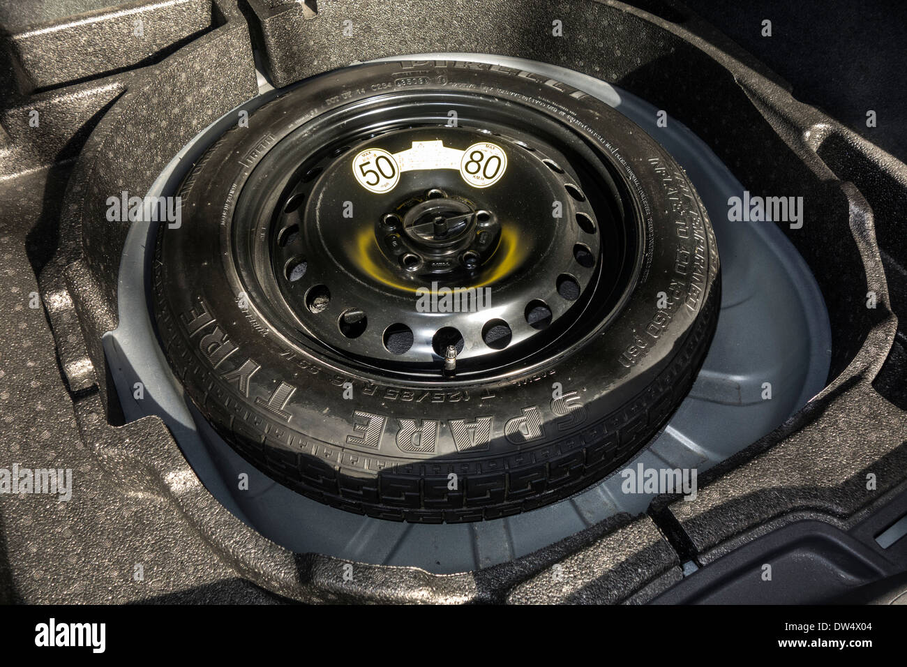 Space-saver spare wheel in trunk of car with limited speed limit of maximum 50 mph / 80 km/h - Stock Image
