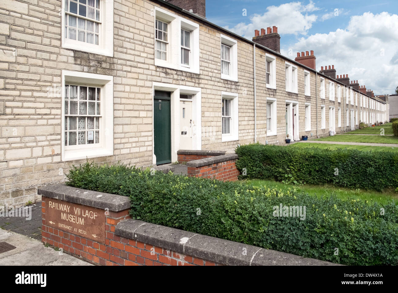 A row of cottages in the preserved historic GWR railway village in Swindon, Wiltshire & the sign to the museum - Stock Image