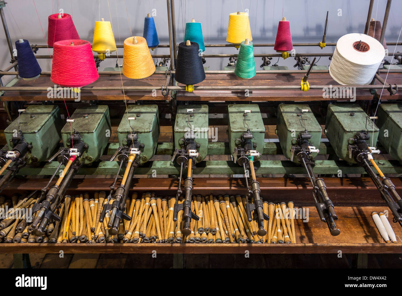 Colourful bobbins with yarn on spool machine in cotton mill at MIAT, industrial archaeology museum, Ghent, Belgium - Stock Image