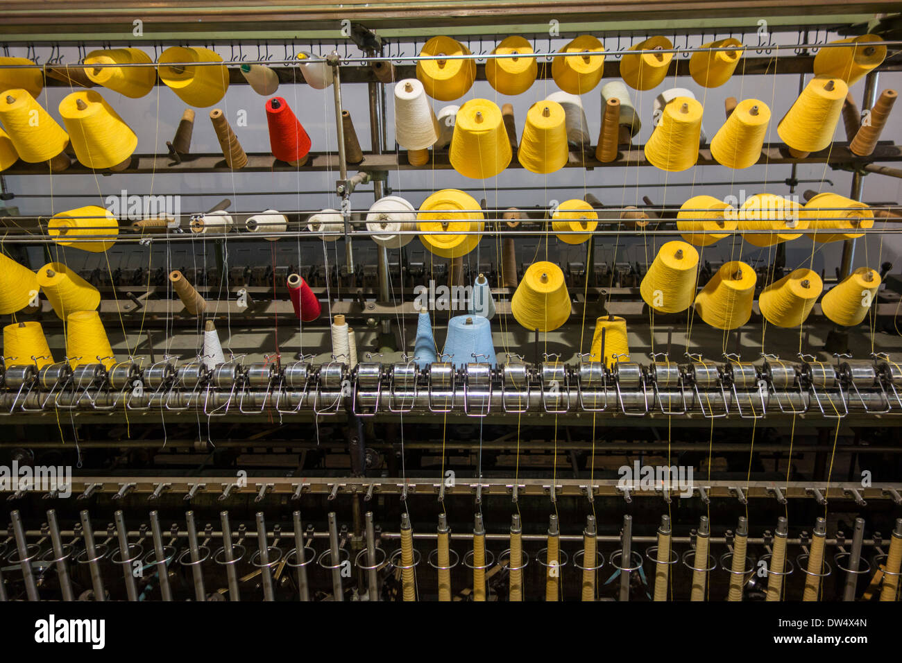 Colorful bobbins with yarn on twisting frame in cotton mill at MIAT, industrial archeology museum, Ghent, Belgium - Stock Image
