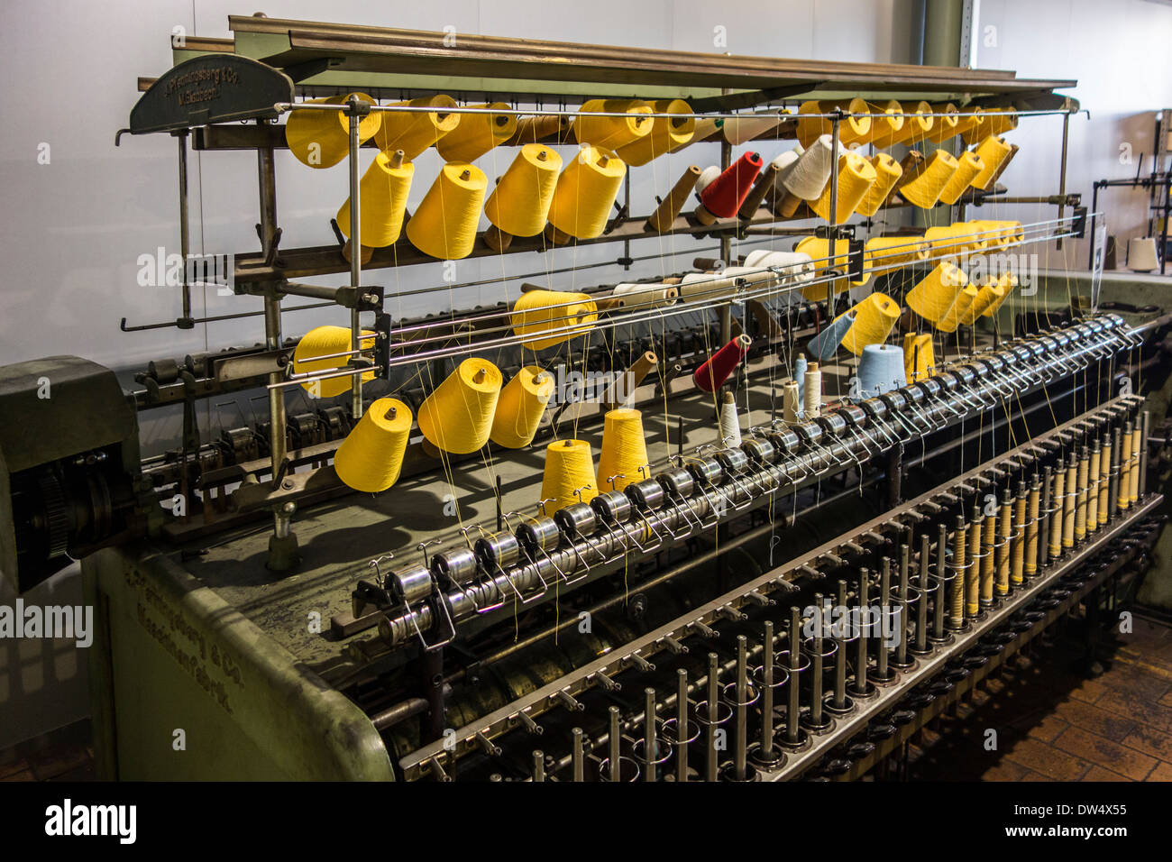 Colourful bobbins with yarn on twisting frame in cotton mill at MIAT, industrial archaeology museum, Ghent, Belgium - Stock Image