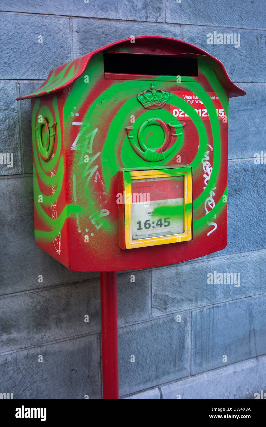 Vandalized postbox / mailbox ruined by graffiti paint by bored youngster in city - Stock Image