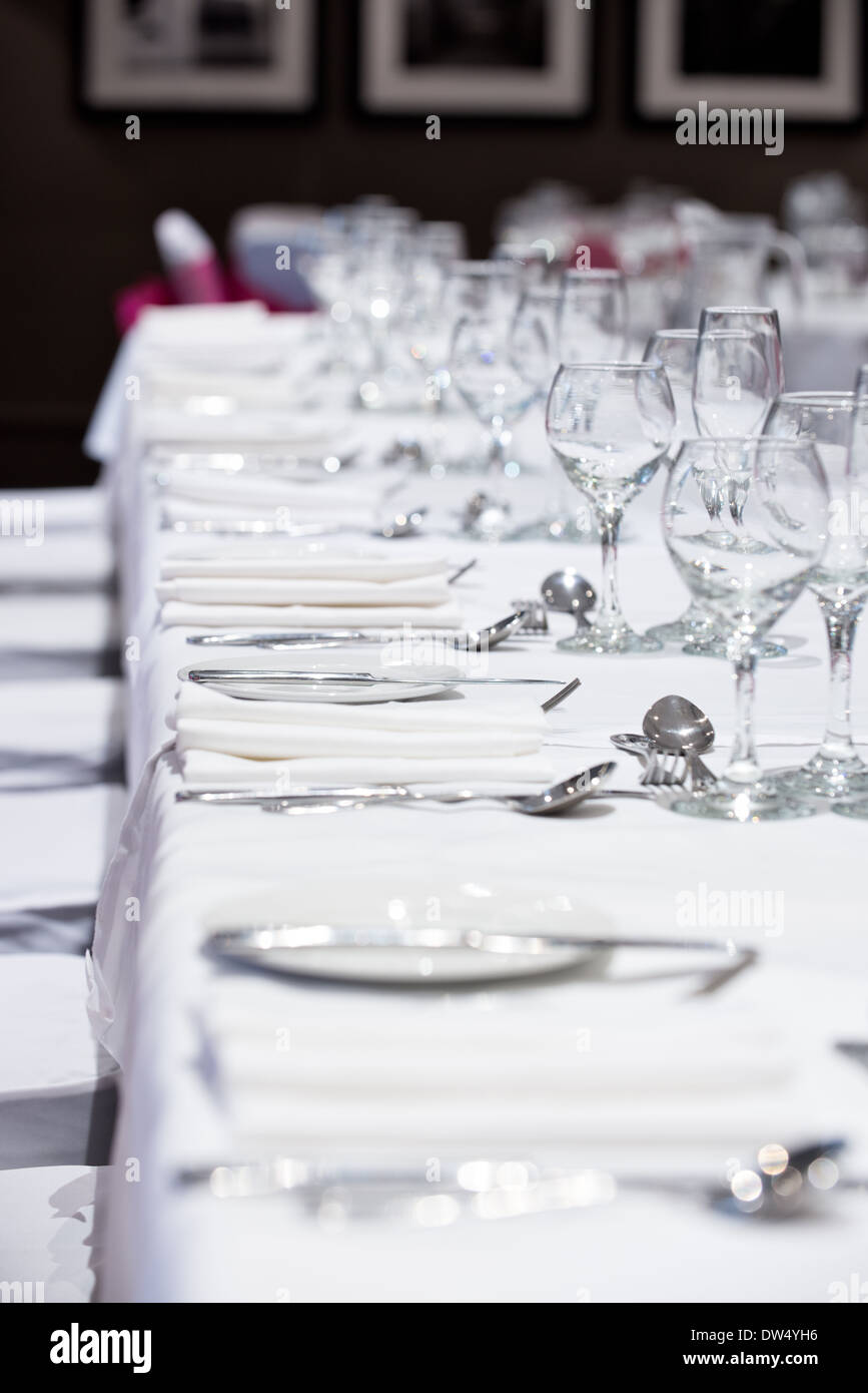 A shallow focus image of a banquet tables place settings & wine glasses awaiting the arrival of the dinners - Stock Image