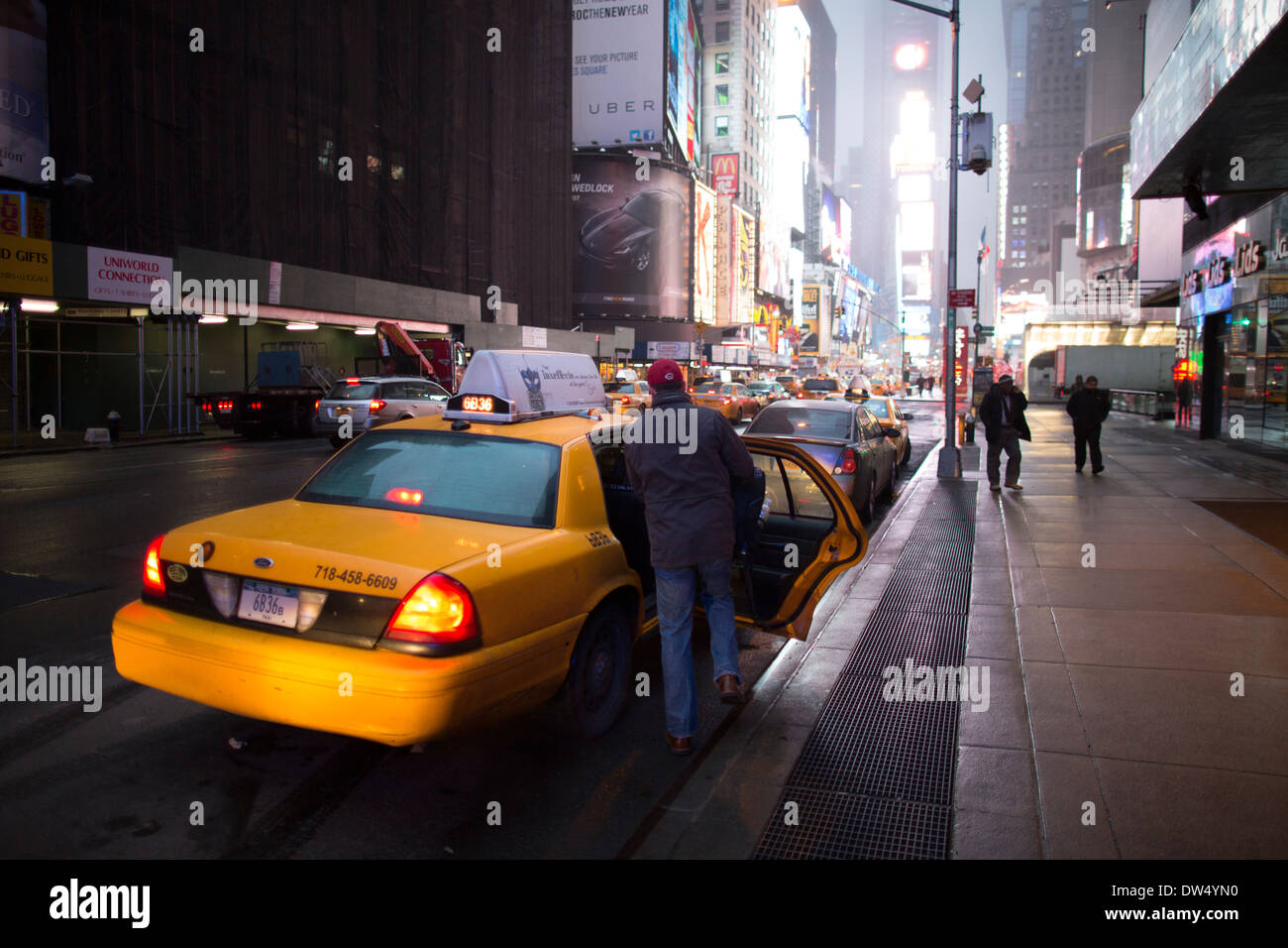 Passenger leaves his yellow cab in Times Square USA Stock Photo