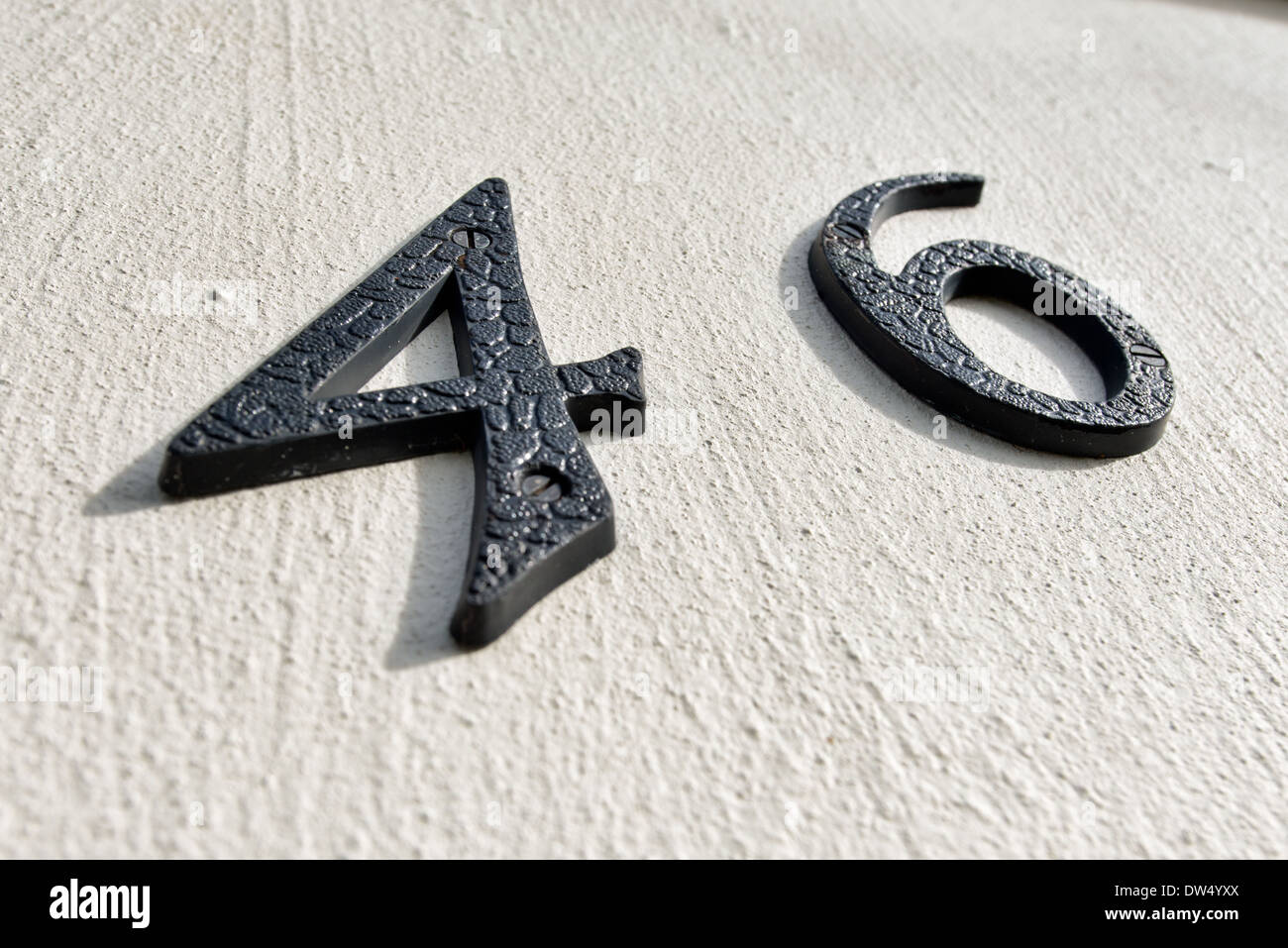 The number forty six using black plastic letters on an off white stucco wall - Stock Image