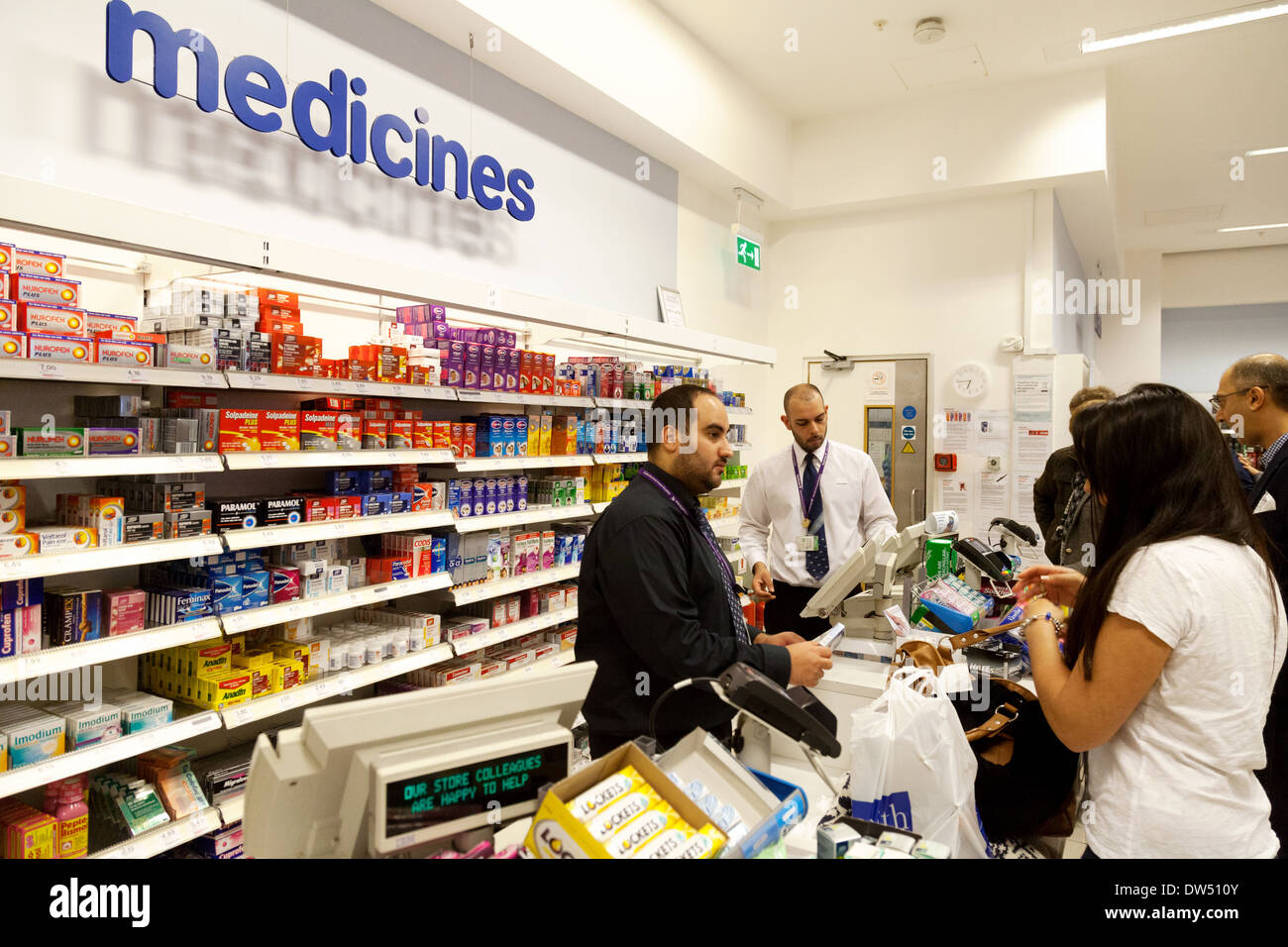 A woman buying medicines from the chemist counter, Boots the Chemist,  UK - Stock Image