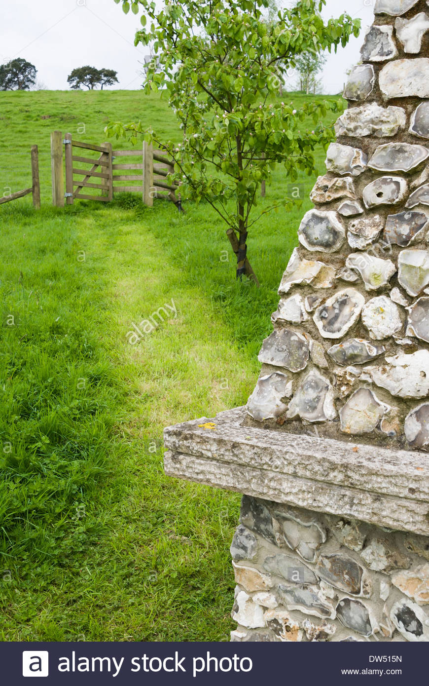 Stone And Flint Obelisk With Path Leading To Gate Into Surrounding  Farmland. Private Garden, Dorset, UK