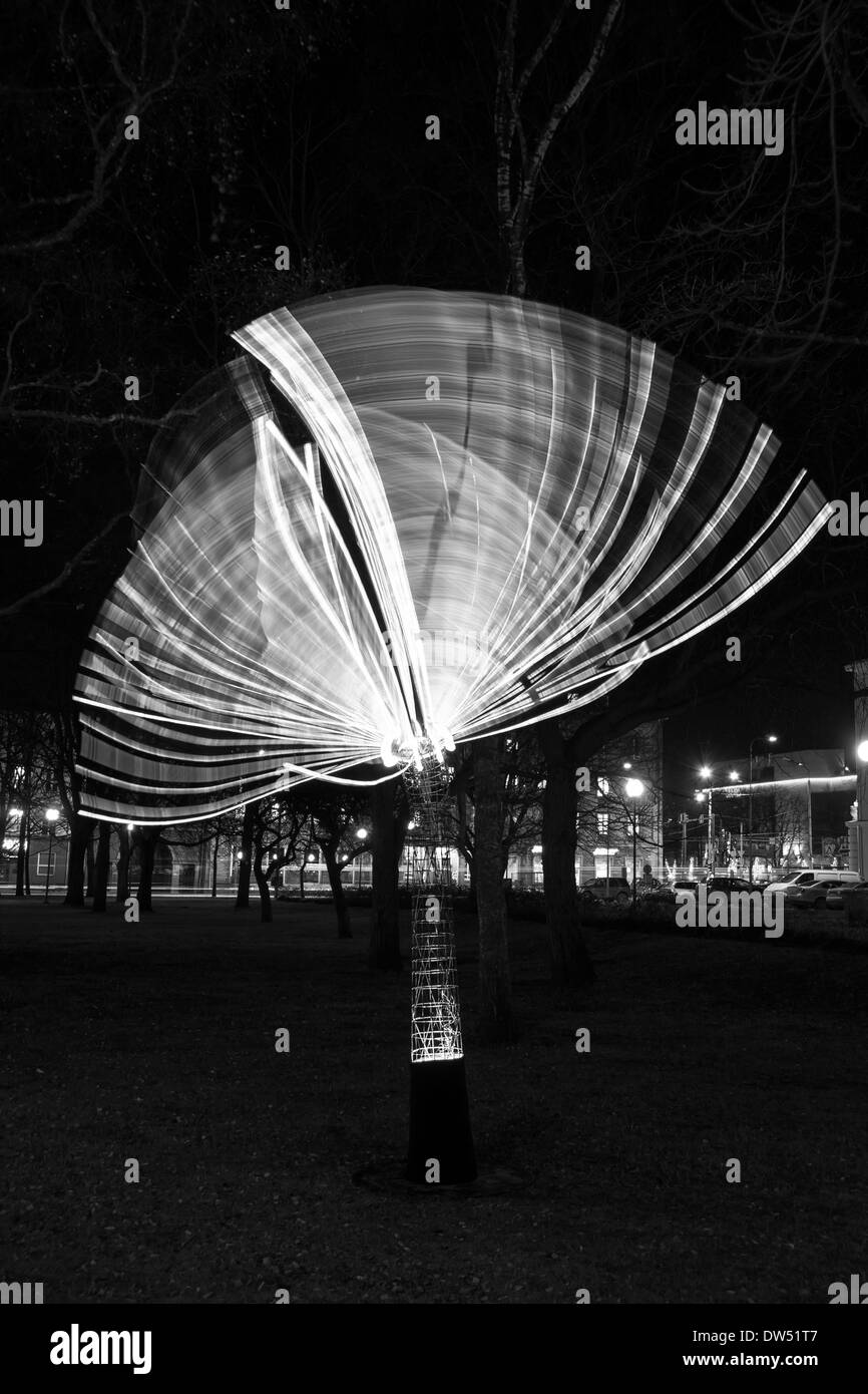 Artificial tree made of light bulbs that moves and leaves light trails behind - Stock Image