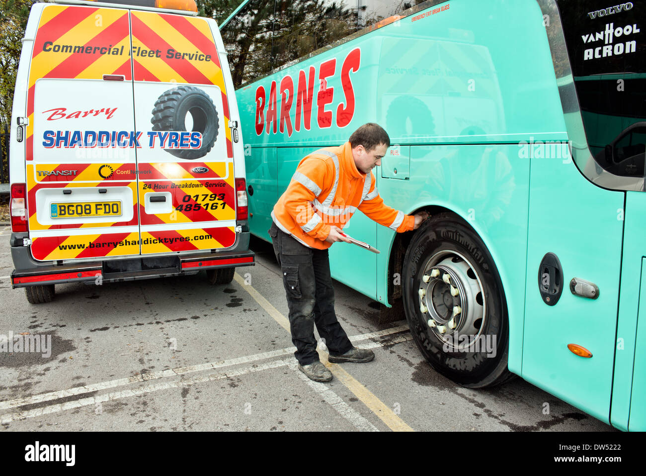 A mobile mechanic / tyre fitter checks a coaches continental tire for tread depth during a regular service & safety inspection - Stock Image