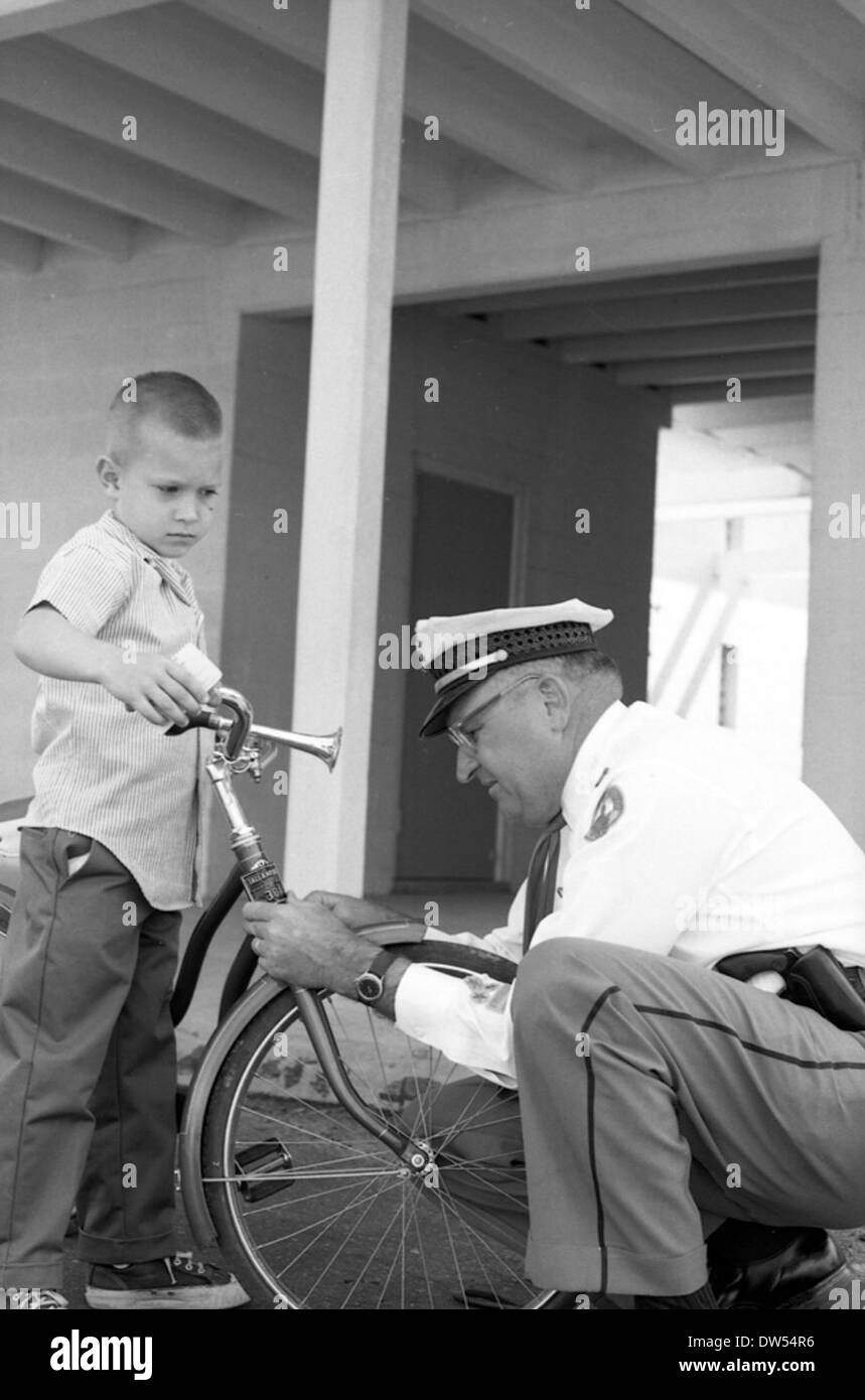 Sergeant Sid Keller inspecting Lloyd Mitchell's bicycle in Tallahassee, Florida - Stock Image