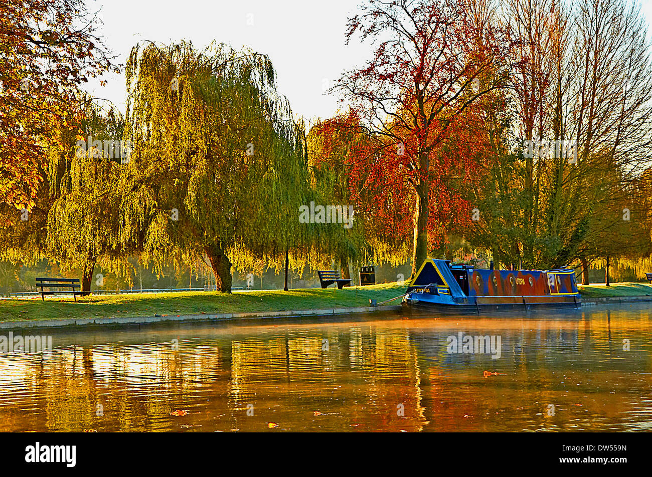 An early morning autumnal river scene with a lone narrowboat moored to the banks of the River Avon, in Stratford upon Avon, Warwickshire. - Stock Image