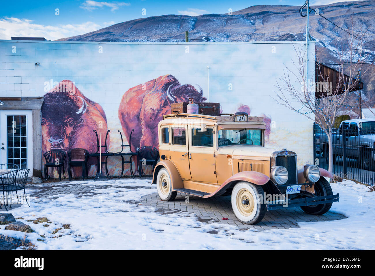 Bison mural and vintage Chevrolet taxi cab, Ashcroft, British Columbia, Canada - Stock Image