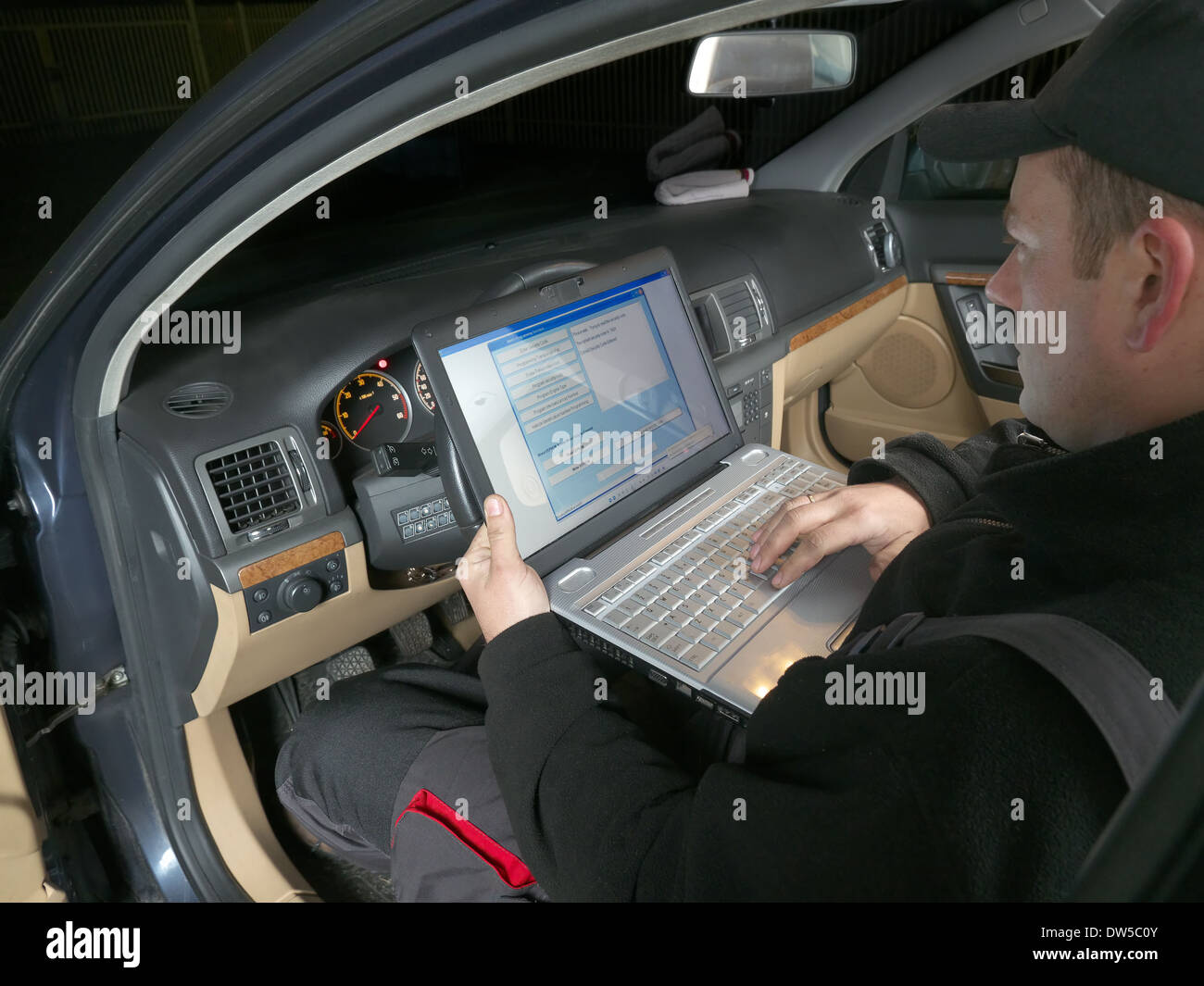 Auto mechanic checking vehicle identification number of the car using laptop hooked up to the car onboard computer - Stock Image