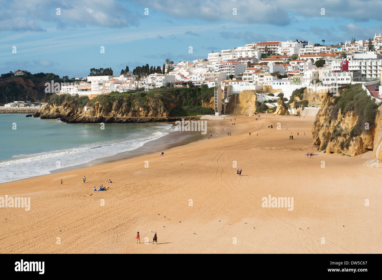 the sandy beach and white painted town at albufeira algarve stock