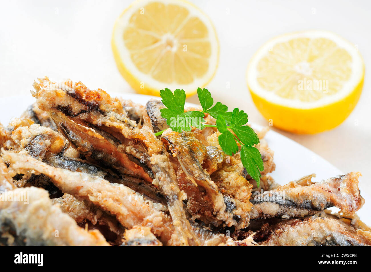 closeup of a plate with spanish boquerones fritos, battered and fried anchovies typical in Spain - Stock Image