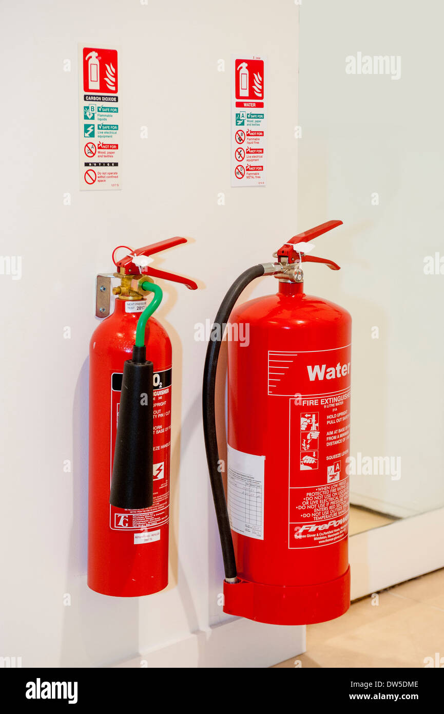 Carbon Dioxide and Water Fire Extinguishers on wall in office - Stock Image