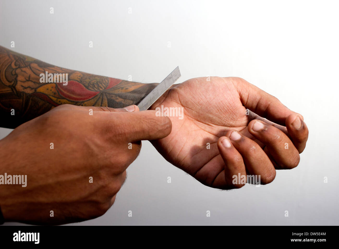Male with tattoos slitting wrist - Stock Image