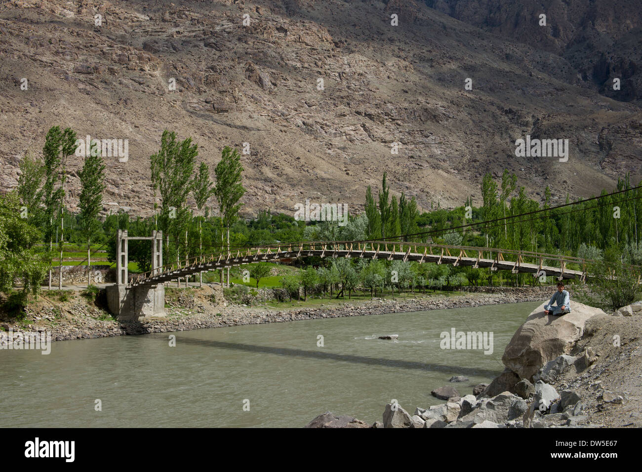 Man sitting next to a suspension bridge over the Ghizar River (Gilgit River) near Sumal Gah, seen from the Shandur-Gilgit Road, Gilgit-Baltistan, Pakistan - Stock Image