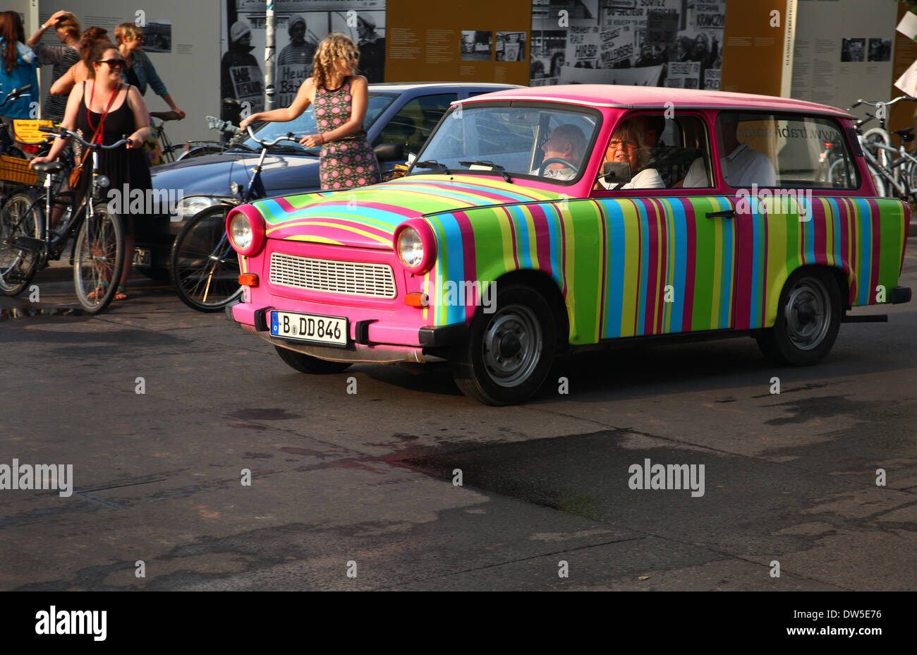 Tourists drive in an East German Trabant car at Checkpoint Charlie in Berlin, August 10, 2013. More and more tourists come to the German capital every year. The photo is part of a series on tourism in Berlin. Photo. Wolfram Steinberg dpa - Stock Image