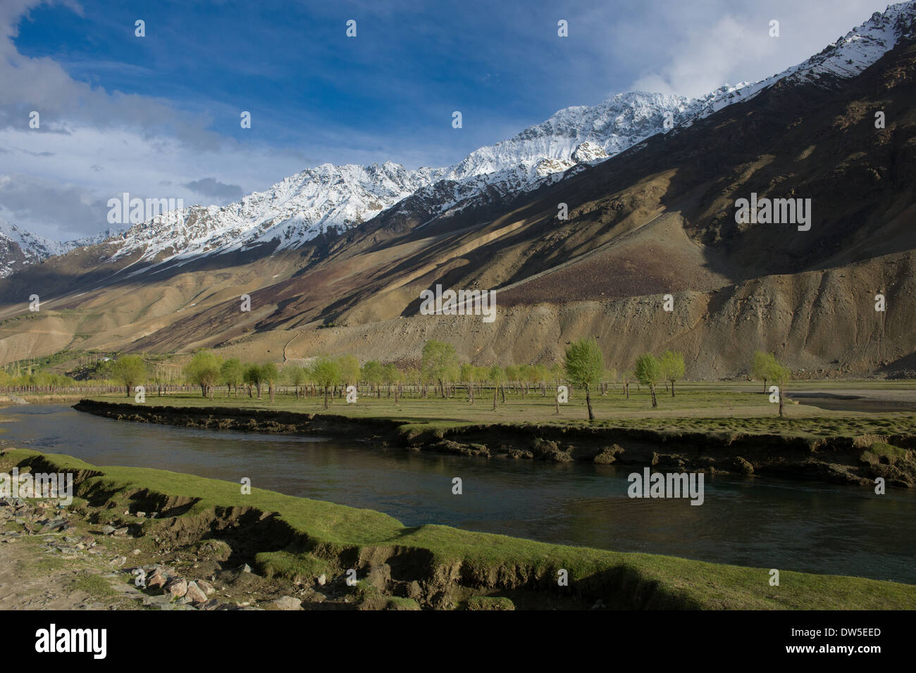 Snow-capped mountains rising above the Ghizar River (Gilgit River) near Terich, seen from the Shandur-Gilgit Road, near the Shandur Pass, Gilgit-Baltistan, Pakistan - Stock Image